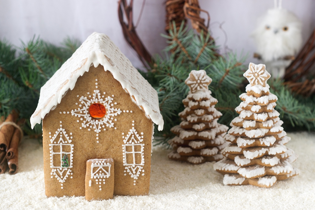 Gingerbread house and gingerbread tree on a light background. Selective focus.