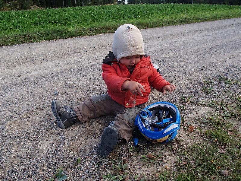 ребенок в походе насыпает песок в велосипедный шлем