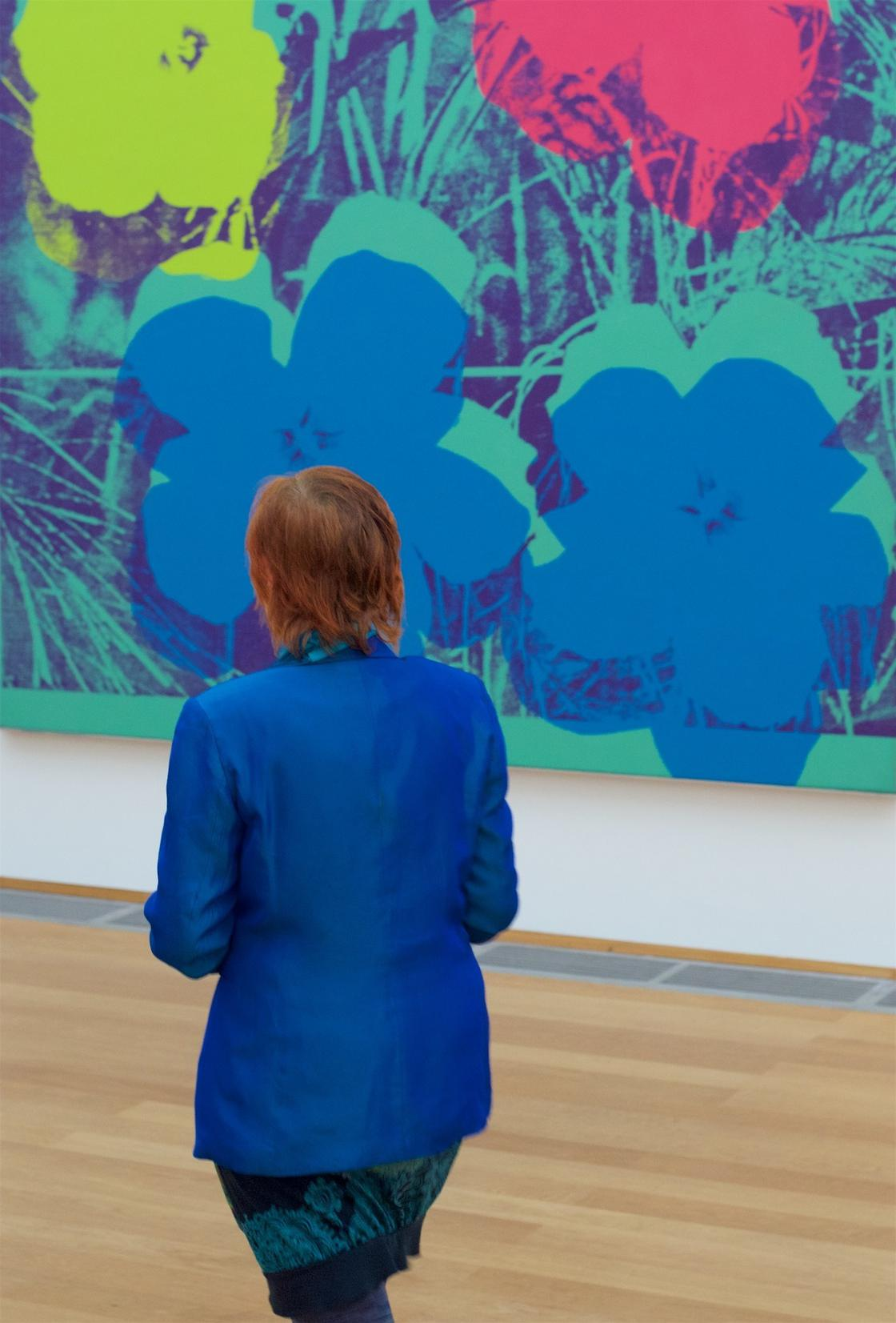 He captures the similarities between the paintings and the visitors