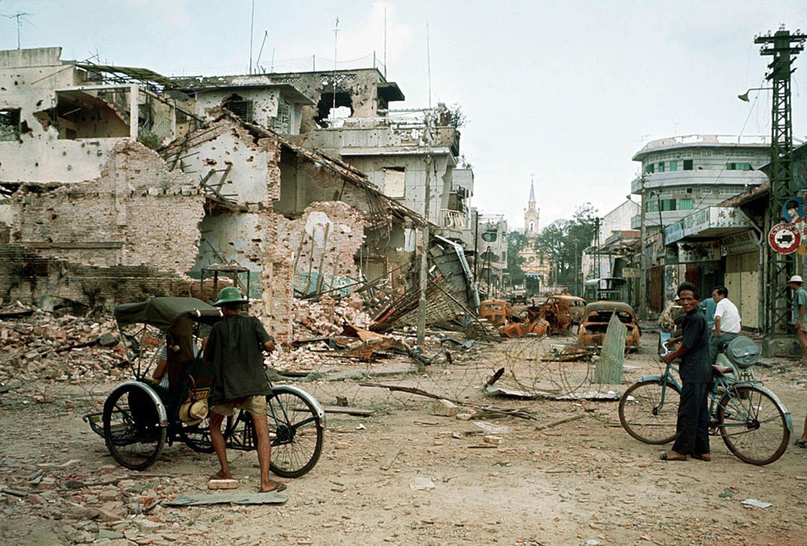 Район Тёлон после того, как большая часть боёв закончилась. Люди со своими велосипедами (один из них рикша) стоят посреди улицы с сильно поврежденными зданиями слева. 10 июня