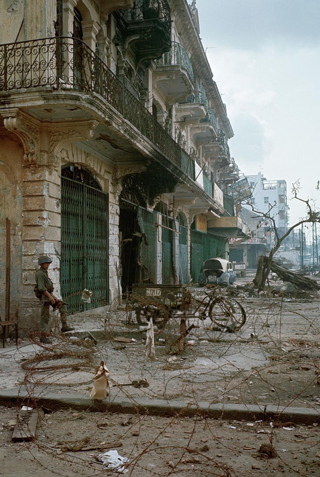 Район Тёлон после того, как большая часть боёв закончилась. Солдат стоит рядом с поврежденным зданием на улице, усыпанной щебнем. 10 июня