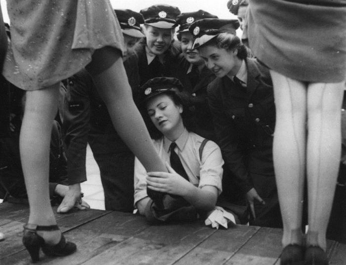 Женщины-военнослужащие рассматривают чулки из искусственного шелка, специально разработаны для армии
