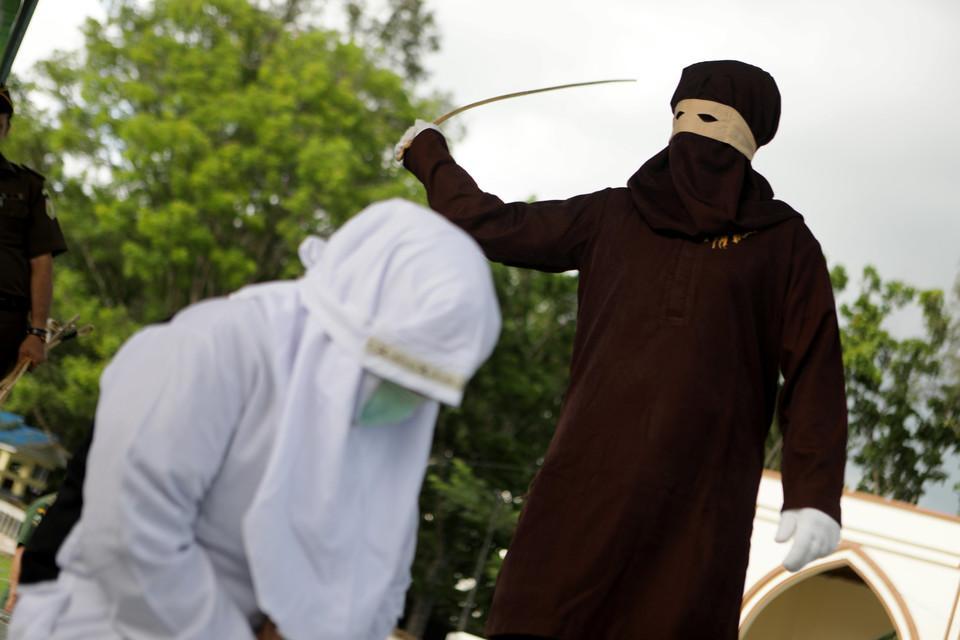 По законам Шариата: в Индонезии десять человек наказали за прелюбодеяние (7 фото)