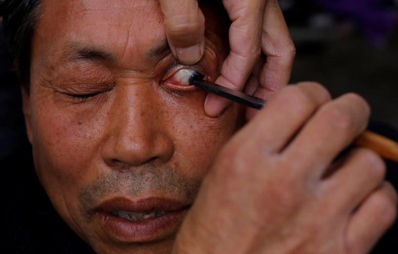 Китайский уличный парикмахер чистит глаза клиентов опасной бритвой