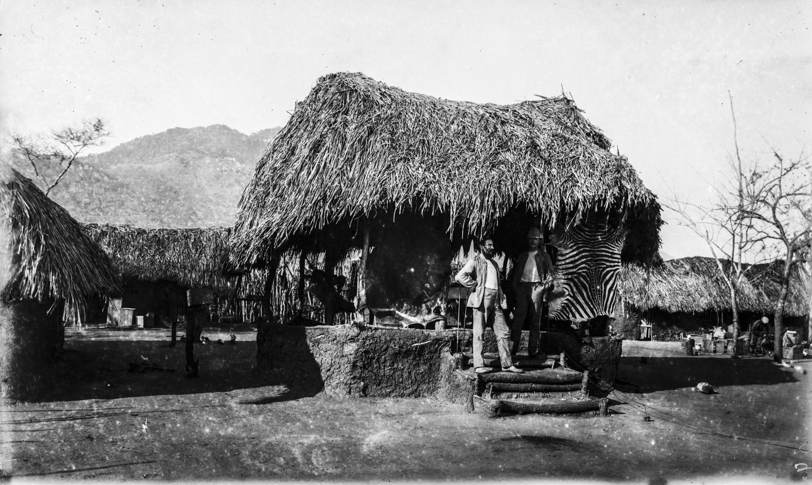 38. Два исследователя стоят в доме немецкого общества Восточной Африки (ДОАГ) станции Мафи