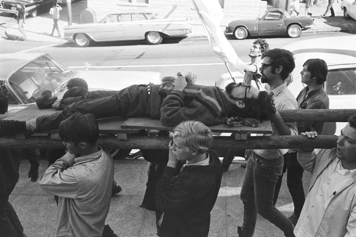1967. Группа людей несут человека, лежащего на носилках во время церемонии «Смерть хиппи». Хейт-Эшбери, Сан-Франциско