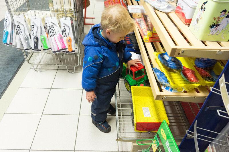 ребенок смотрит на игрушечный трактор в магазине