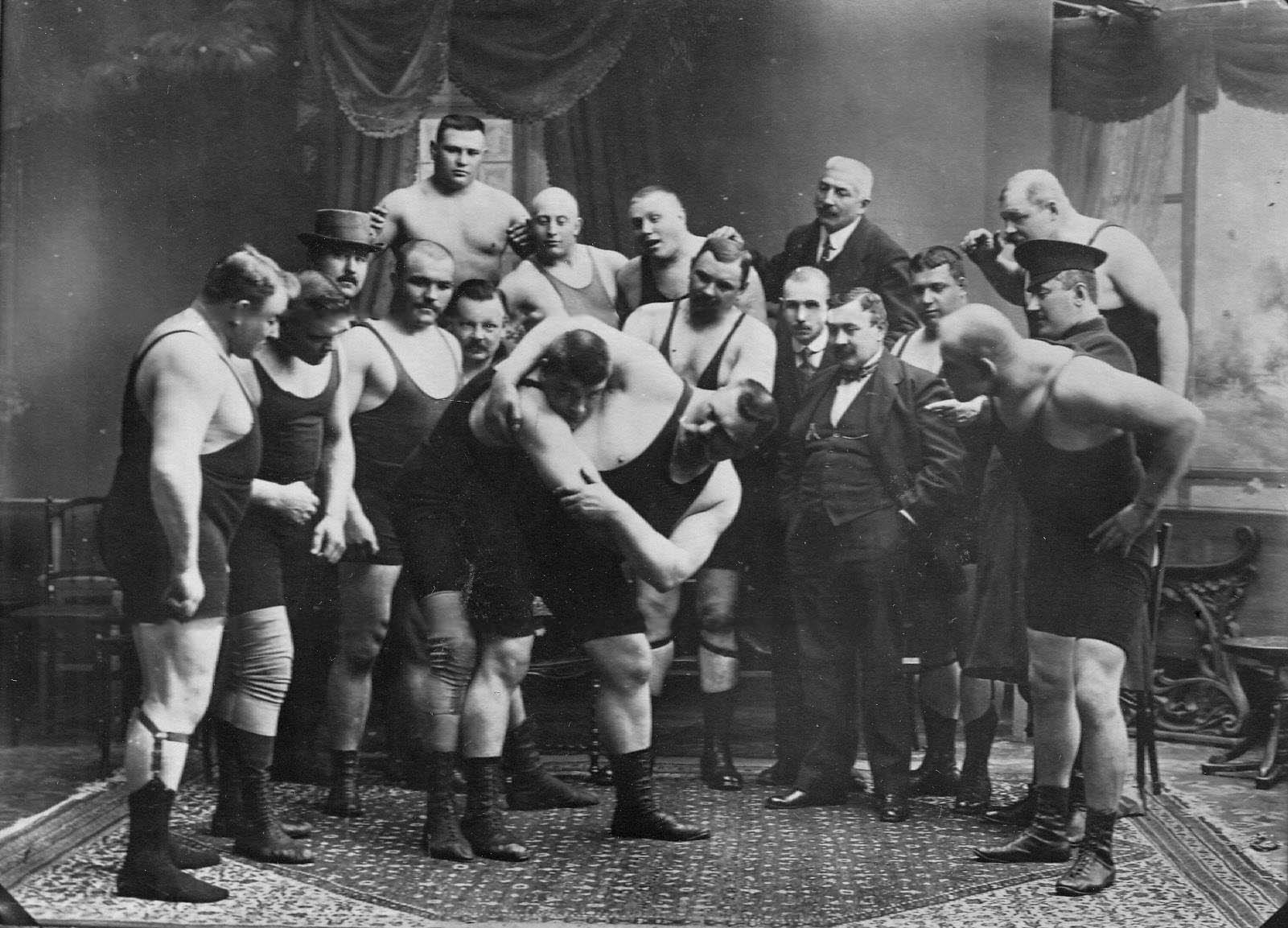Группа участников чемпионата наблюдает за борьбой двух борцов; борец справа - И.М.Поддубный