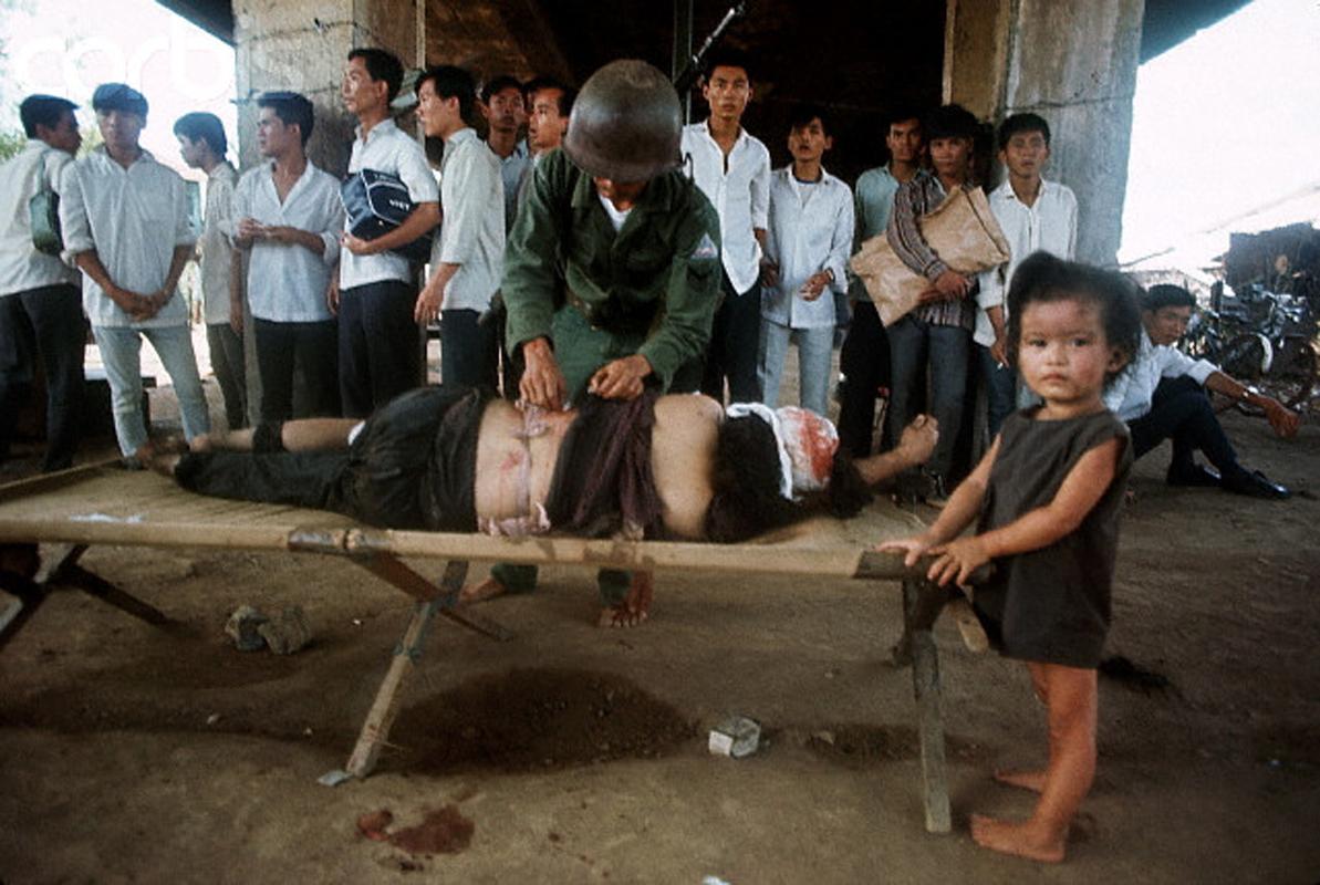 Ребенок по-прежнему находится рядом с ее раненой матерью, которой оказывает помощь военный медик в районе Тёлон. 7 мая