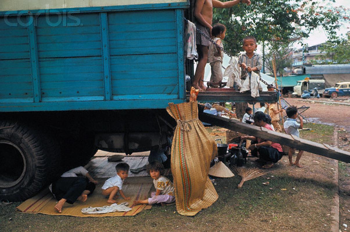 Беженцы используют этот грузовик в качестве временного убежища, в нескольких кварталах от их горящих домов, в районе Тёлон. 15 мая