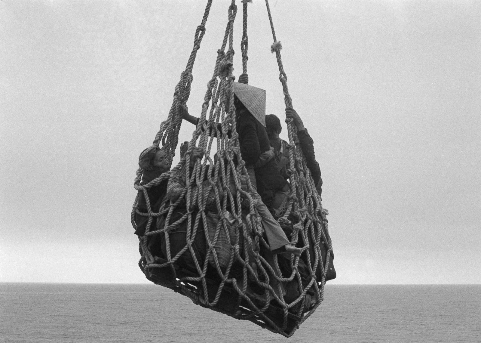 Грузовая сеть поднимает беженцев с баржи на корабль в Донанге. 1 апреля 1974