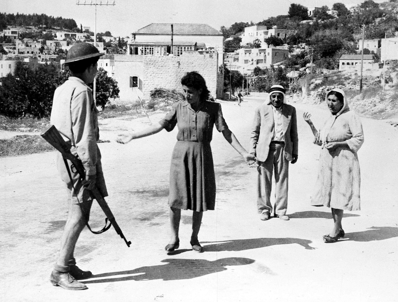 Солдат, вооруженный винтовкой, останавливает арабов на улице в Назарете, поскольку они перемещаются после наступления комендантского часа. В тот день израильские силы оккупировали город. 17 июля