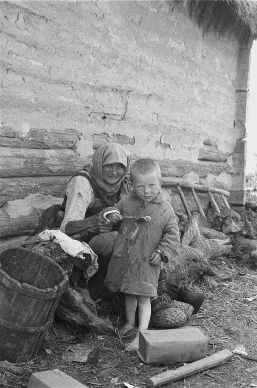 Старушка с маленьким мальчиком перед домом