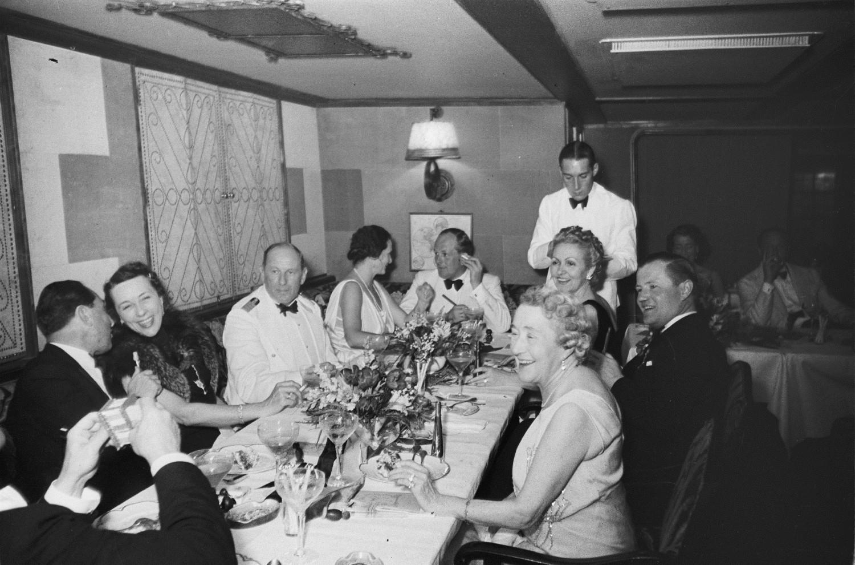 Пассажиры и члены экипажа за праздничным столом