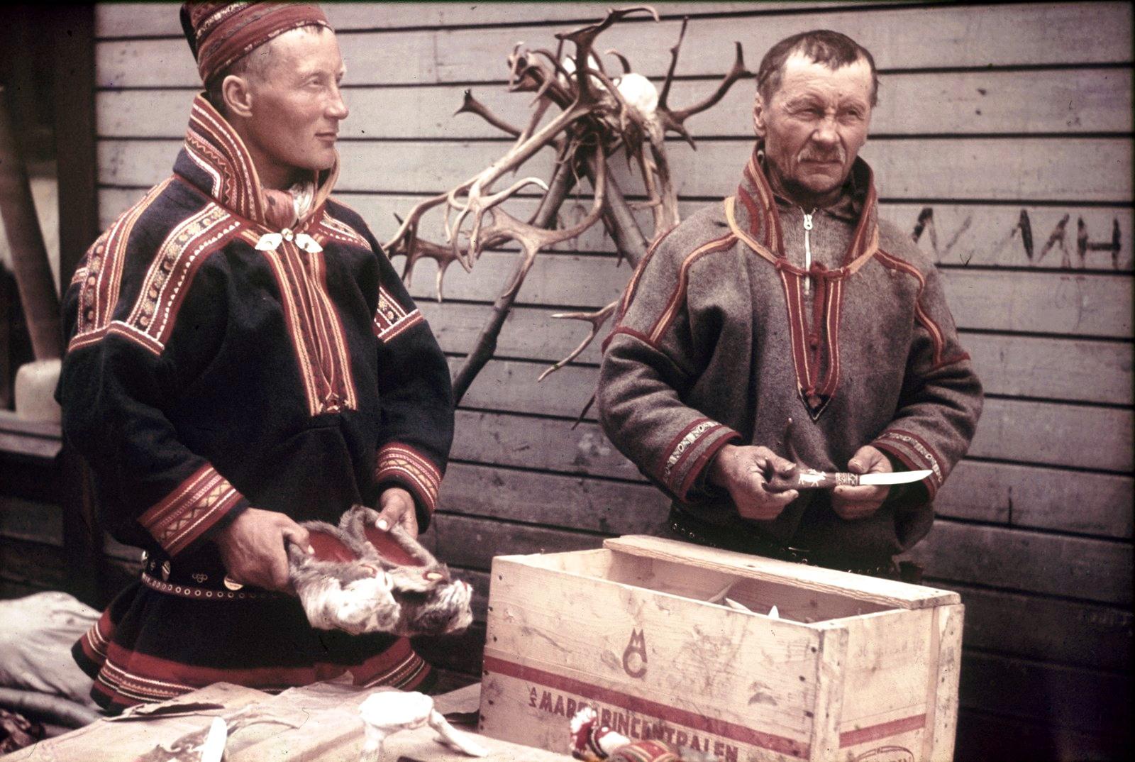Два саама в национальных костюмах возле сувенирной лавки