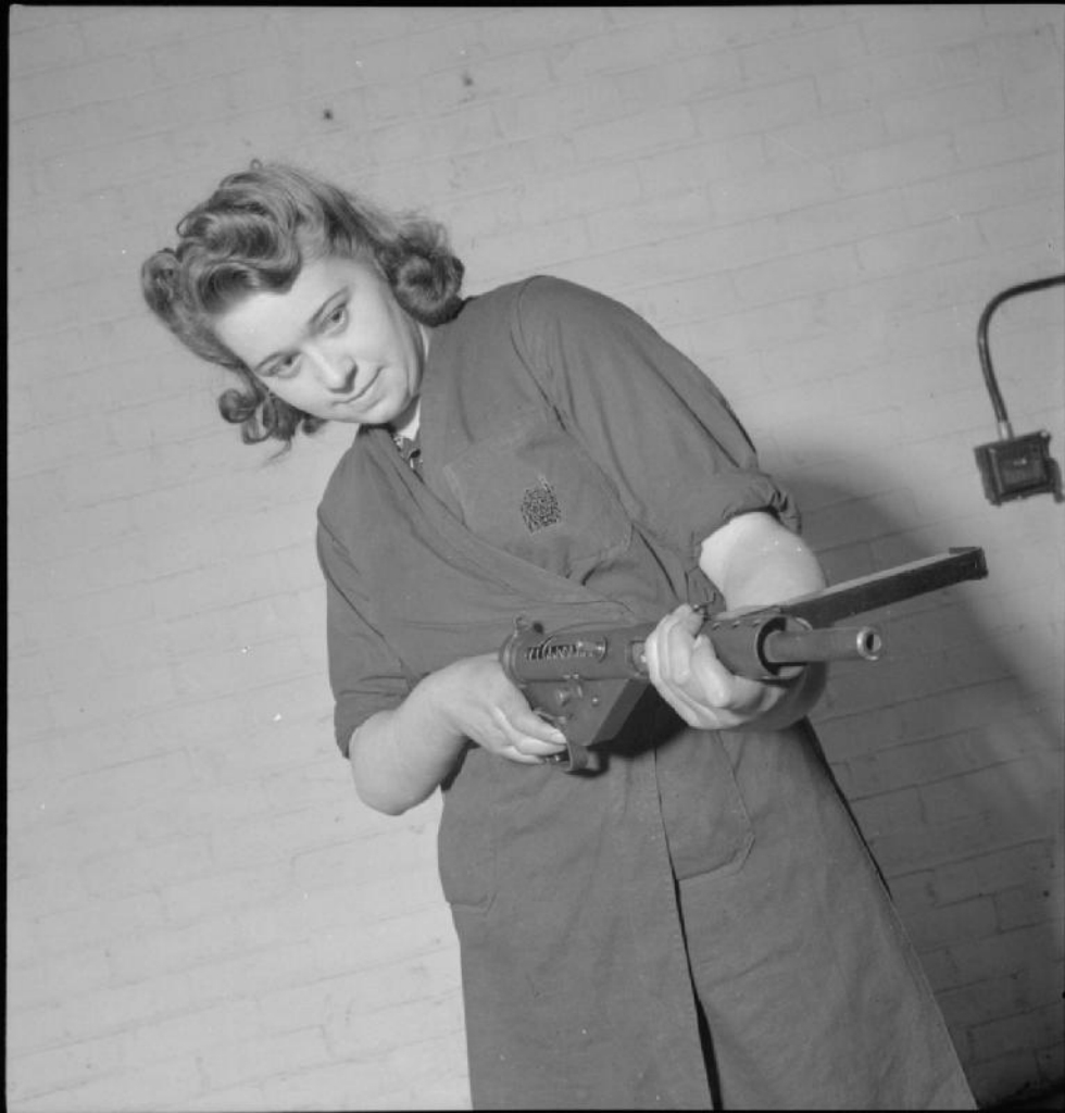 A Belgian worker assembles a Sten gun at an ordnance factory, somewhere in Britain.jpg