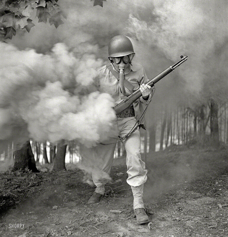 September 1942. Fort Belvoir, Virginia. Sergeant George Camblair learning how to use a gas mask in a practice smokescreen