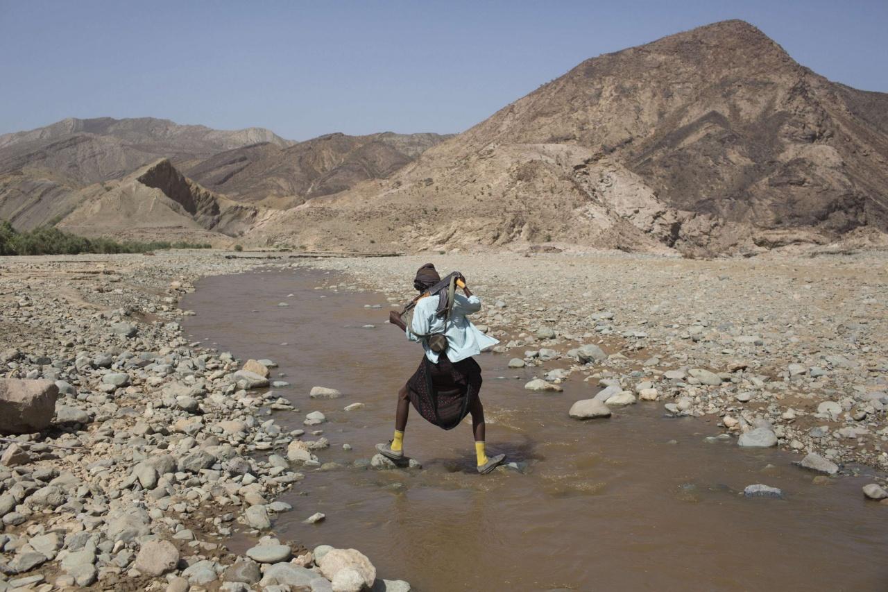 An armed Afar man crosses a river near the Danakil Depression, northern Ethiopia