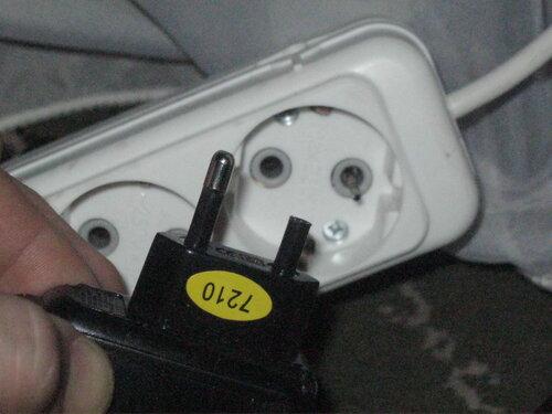 Фото 4. Повреждённое зарядное устройство и торчащий из колодки удлинителя штырь. Первый ракурс.