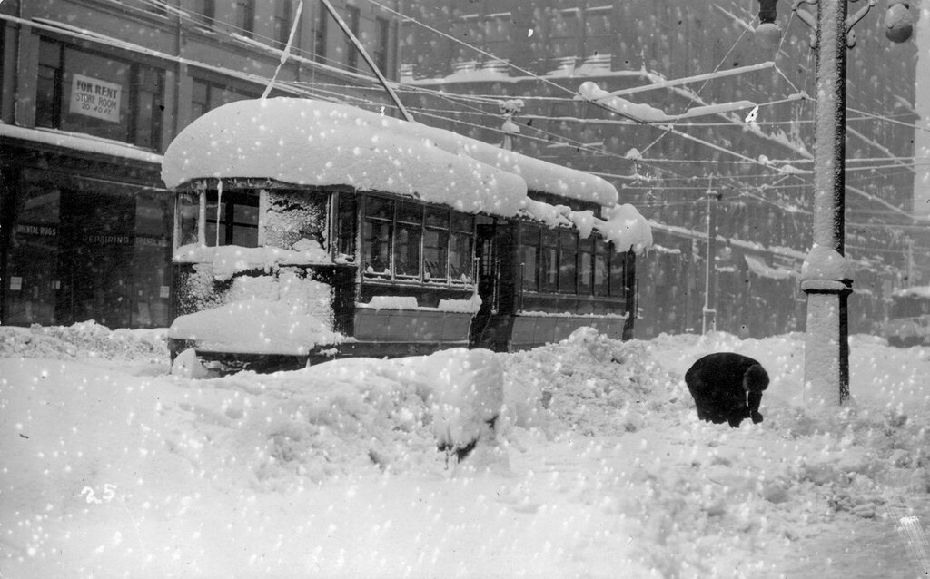 A snow covered Denver City Tramway trolley car is stuck in the snowstorm of 1913 in central Denver, Colorado. 1913.