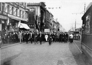 Манифестанты проходят по Невскому проспекту около магазина Елисеева (д.56).