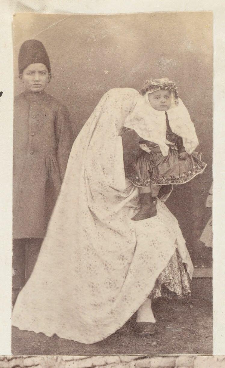 Марьям Ханум в руках женщины рядом с Хасаном, сыном Машхади Гуляма