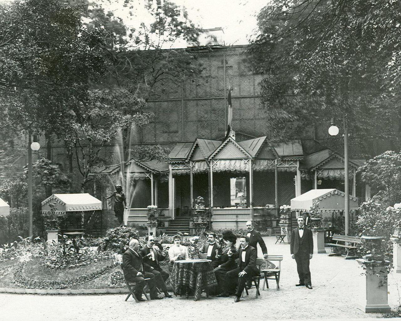 05. Группа посетителей за столом в саду ресторана  «Контан» (крайний слева сидит владелец ресторана Альмир Жуэн)