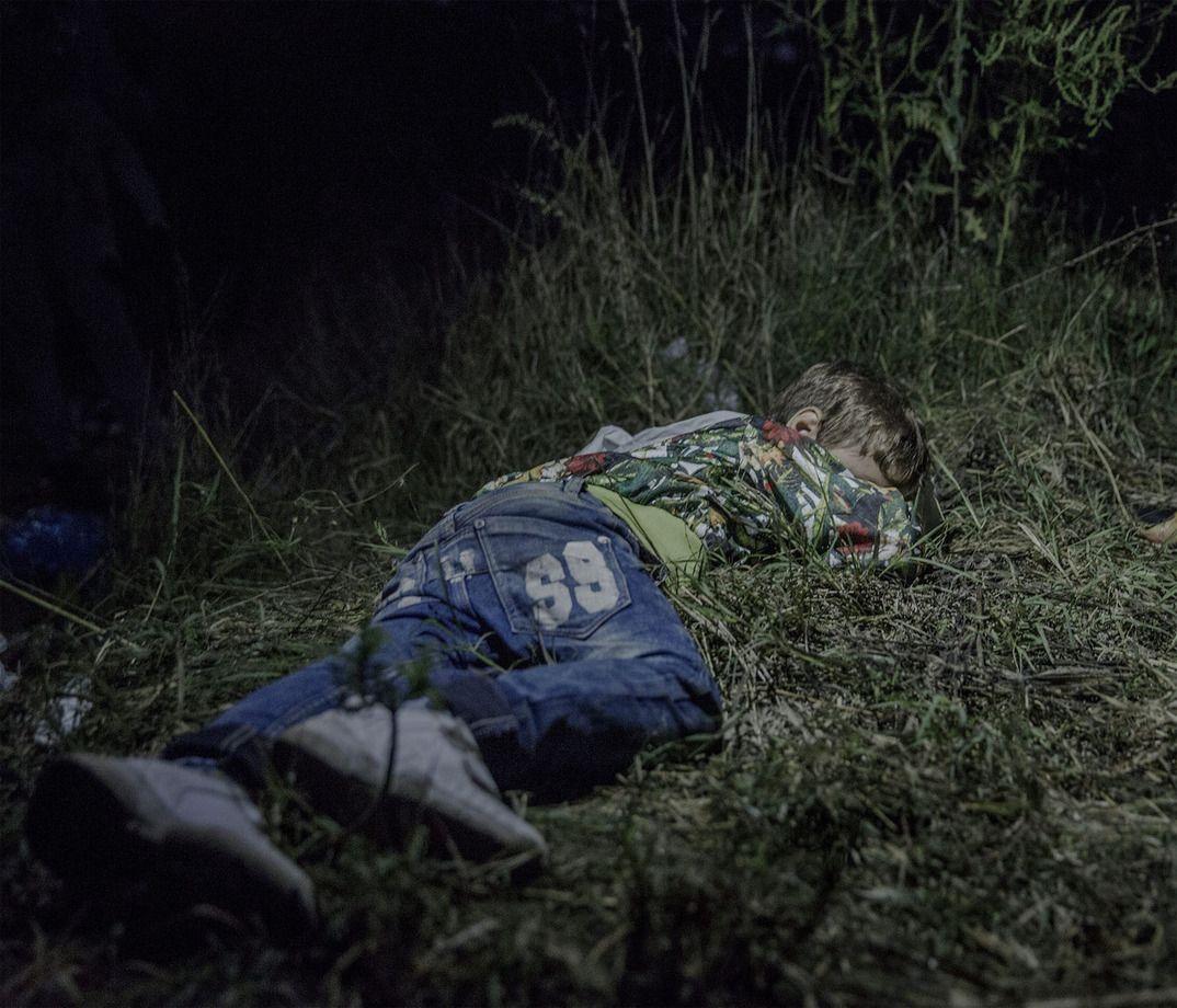 8. Шестилетний Ахмед спит на земле в Хоргоше, Сербия. В пути Ахмед сам несет свою сумку. «Он смелый