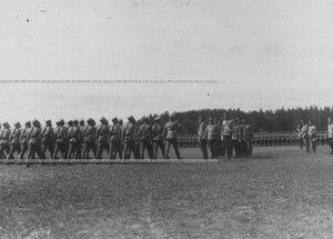 Подразделения юнкеров - выпускников училища проходит церемониальным маршем мимо императора Николая II и его свиты.