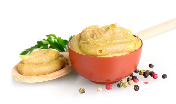 Mustard in bowl and spoon, spices and parsley isolated on white