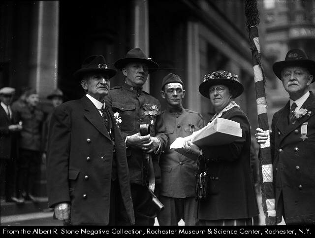 A woman stands with 4 veterans from 3 different wars the Civil War, the Spanish-American War, and WWI, 1916