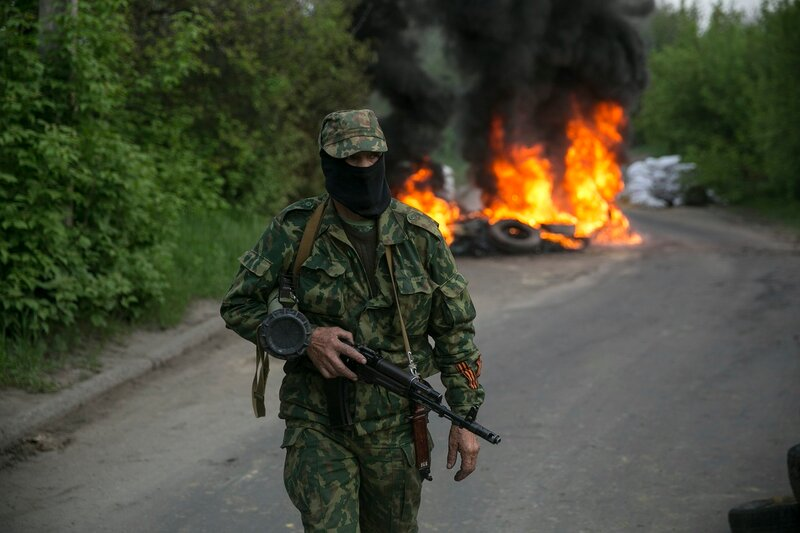 A pro-Russian separatist guards a checkpoint as tyres burn behind him near the town of Slaviansk