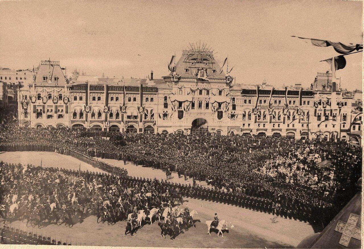 Император Николай II (впереди на белом коне) в сопровождении свиты шествует мимо Средних Торговых рядов на Красной площади в день торжественного въезда в Москву их императорских величеств
