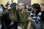 Израильский солдат Елор Азария, которого обвиняют в непредумышленном убийстве раненого палестинца, целуется со своей девушкой в здании суда. Тель-Авив, Израиль, 4 января 2017 года. Фото: Heidi Levine / Pool / Reuters