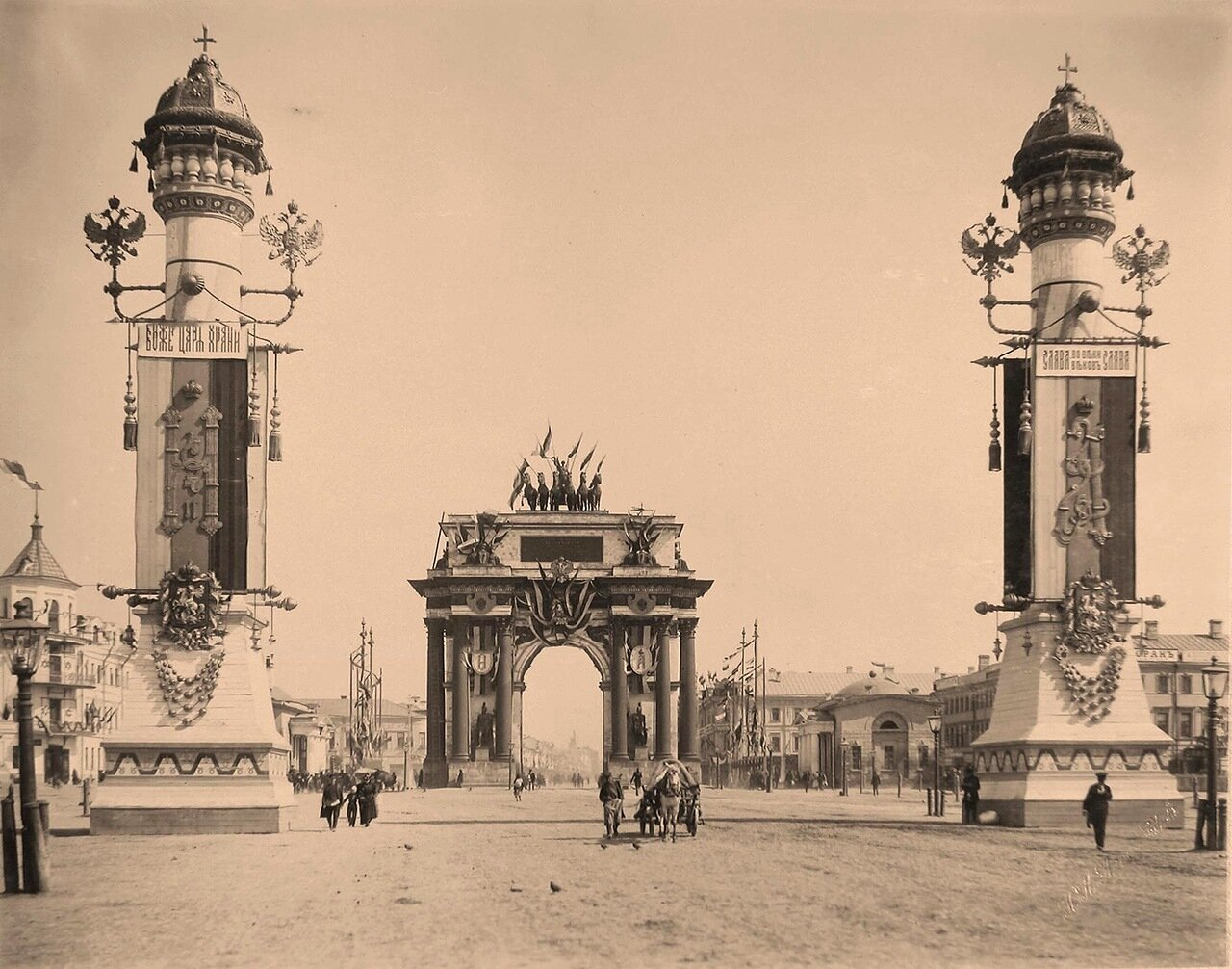 Вид празднично украшенных Триумфальных ворот на площади Тверской заставы; с двух сторон ворот - иллюминированные колонны, увенчанные скульптурными изображениями шапок Мономаха