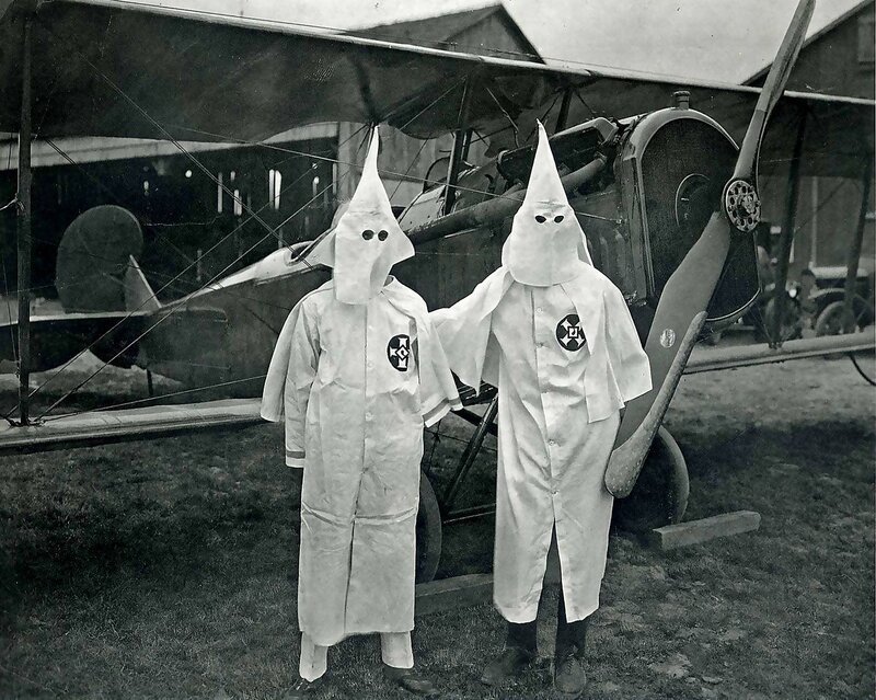 Two Ku Klux Klan member pose with an airplane decorated with glowing crosses that was flown over a KKK rally, 1924.
