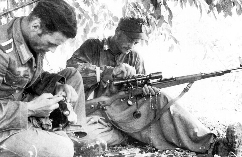 German sniper cleans his Karabiner K98k during a lull in the fighting somewhere in E. Europe.