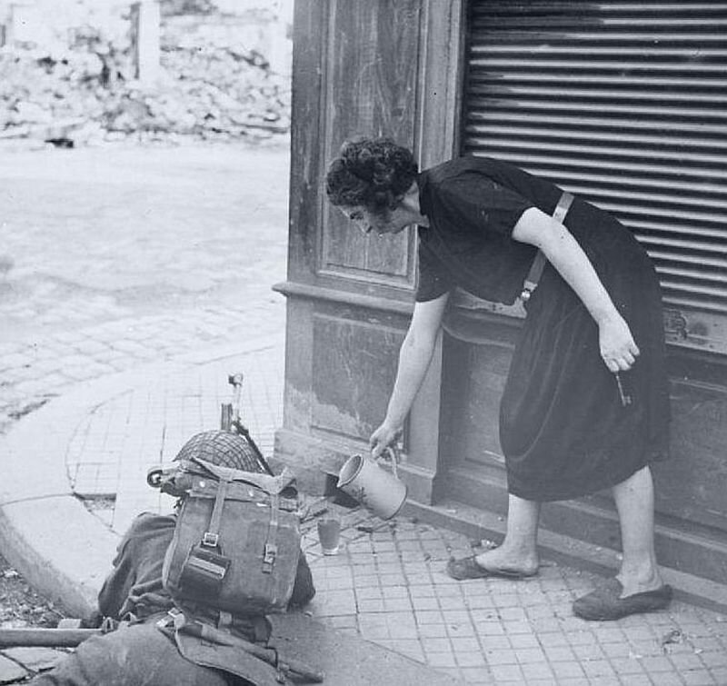A French civilian pours some tea for a British soldier guarding an intersection, August 1944