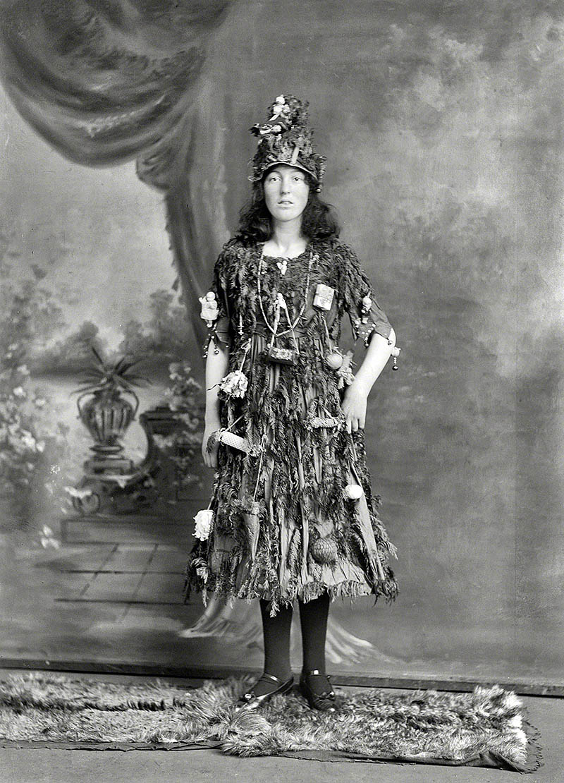 Studio portrait of a young woman in Christmas tree dress and hat costume. Christchurch, New Zealand, 1910.jpg