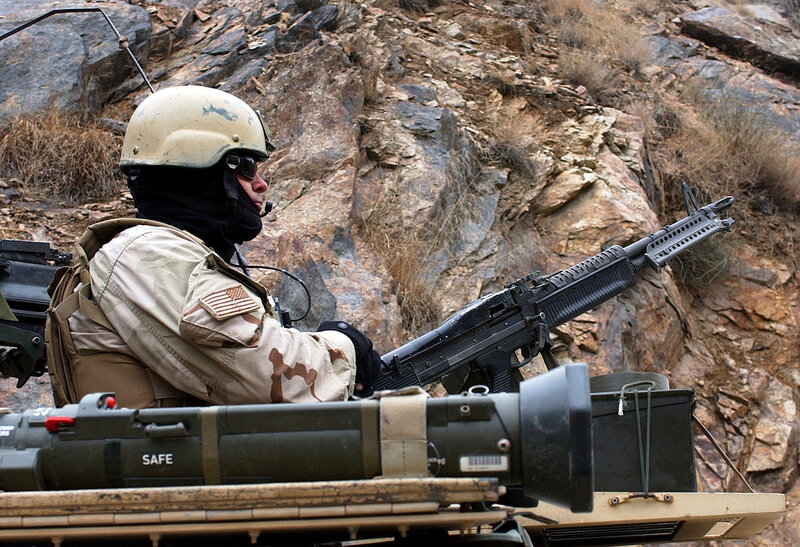 Sgt. First Class Mark Moody from the 19th Special Forces Group (Airborne) mans a M-60 machine gun in the turret of a High Mobility Multipurpose Wheeled Vehicle, while someone changes a truck tire on the way to Asadabad, Afghanistan, Jan. 12th, 2004.  ( U.