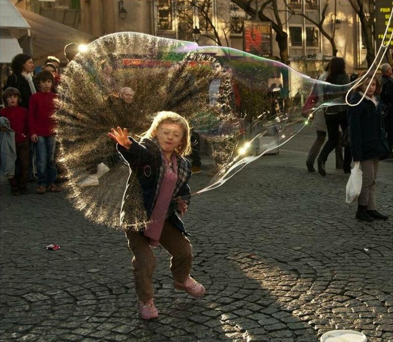 Огромный мыльный пузырь лопается перед маленькой девочкой.