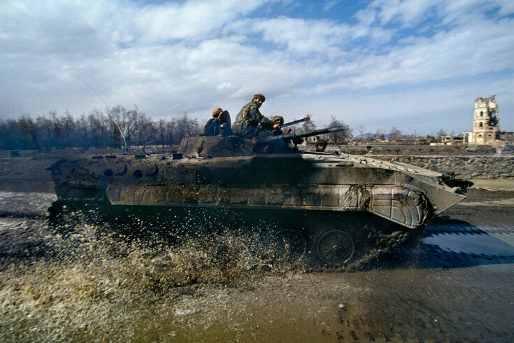 sec02_09_170: March, 1994 Soldiers loyal to President Burhanuddin Rabbani ride along the Kabul River in a BMP-1, a Russian-built armored vehicle.