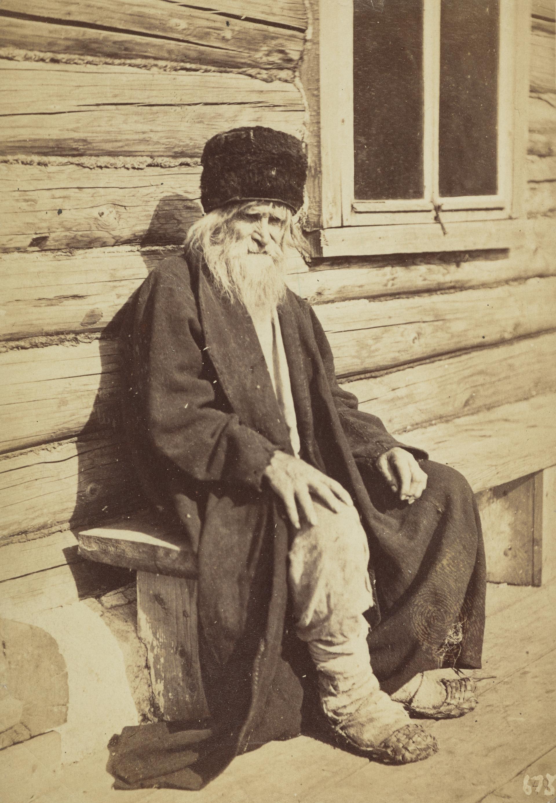 Старый крестьянин на деревянной скамье