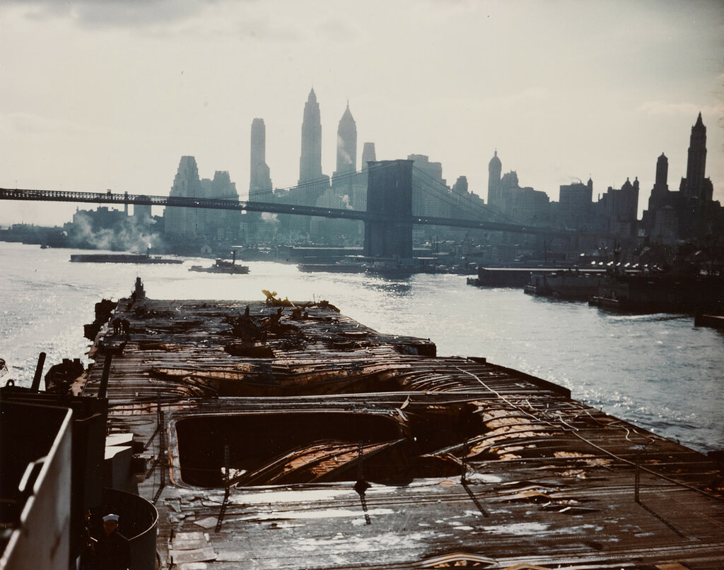 USS Franklin (CV-13). Wrecked flight deck, looking after from the island, as the ship steams up the east river to the New York Navy Yard for repairs. The Brooklyn Bridge and Manhattan skyline are in the background. Sat, Apr 28, 1945.