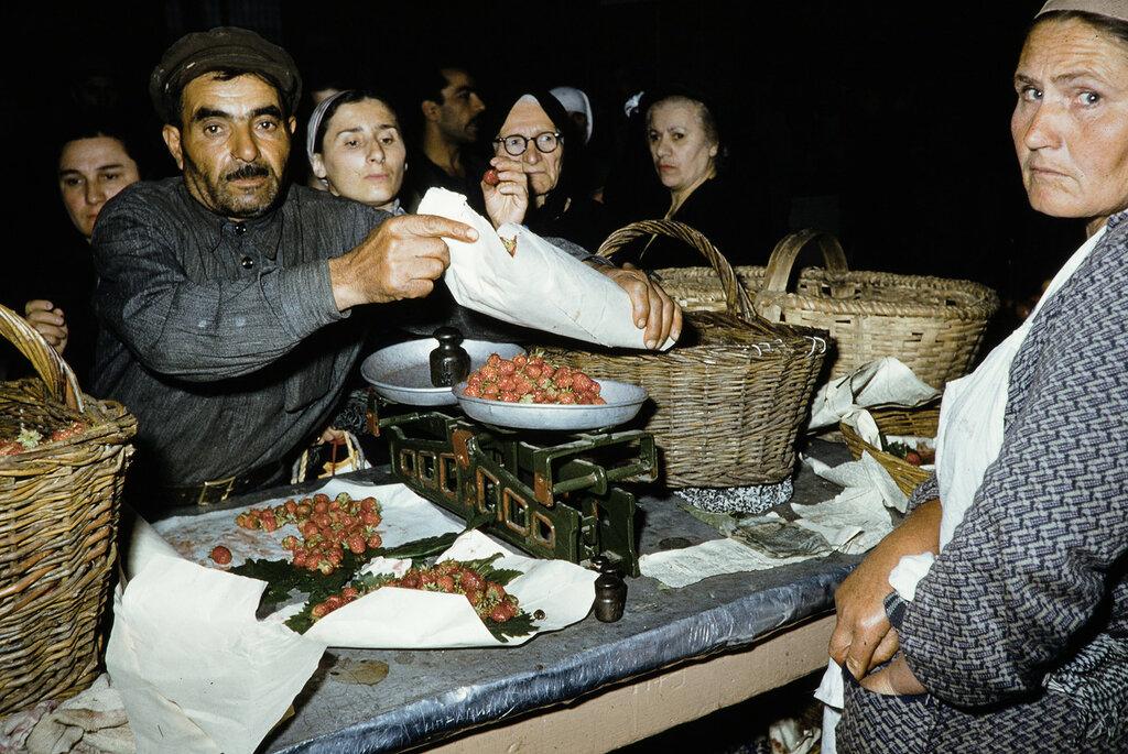 Russia, merchant selling strawberries at market, Georgia