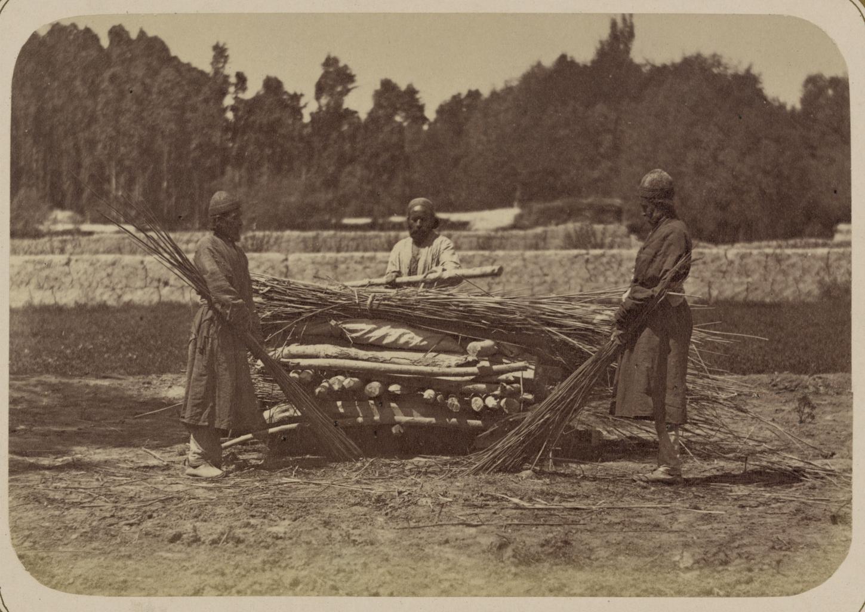 Погребальные обычаи. Индийские похороны. Трое мужчин накладывают хворост поверх тела, лежащего на похоронных дрогах