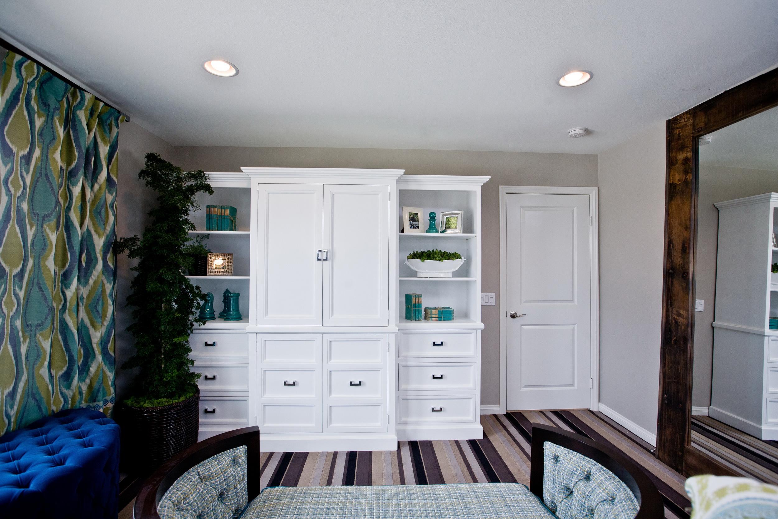 Белый шкаф в спальне. Интерьер в синих, белых и лиловых тонах. Синий пуф, каретная обивка