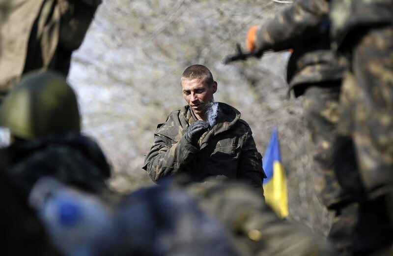 A Ukrainian soldier smokes a cigarette as he sits on an airborne combat vehicle near Kramatorsk