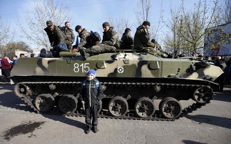 A boy stands in front of Ukrainian soldiers sitting on an airborne combat vehicle in Kramatorsk