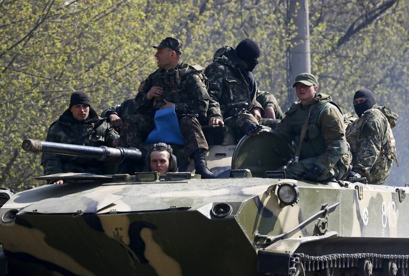 Armed men drive an armoured personnel carrier in Slaviansk